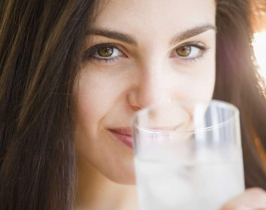 Woman raising a glass of sparkling clean water