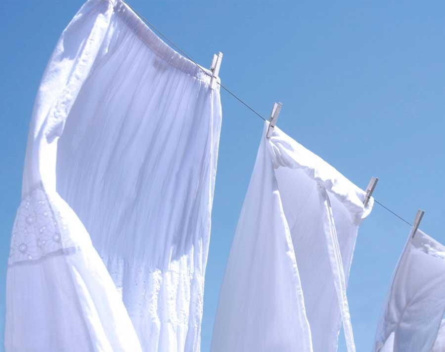 Bright white linens drying on a clothesline