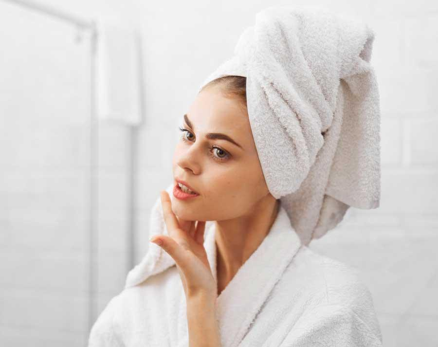 Woman after shower in bright white robe and towel