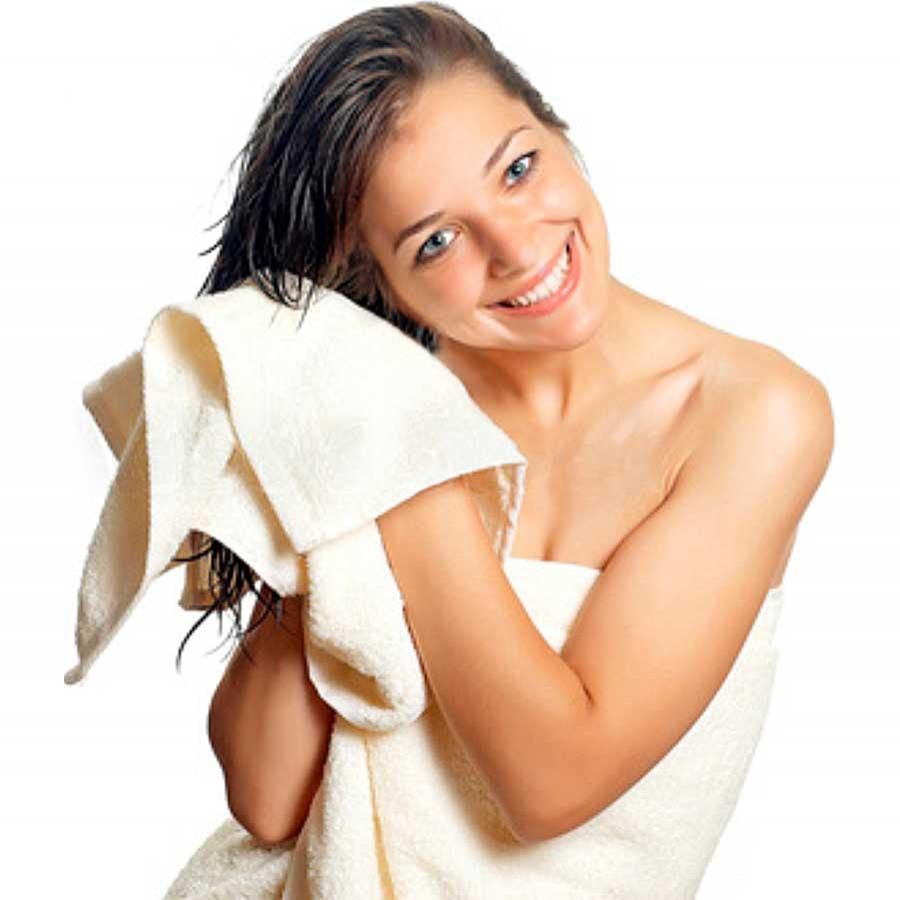Woman drying hair with white towel. Water Ways Baja purification systems make your whites whiter.